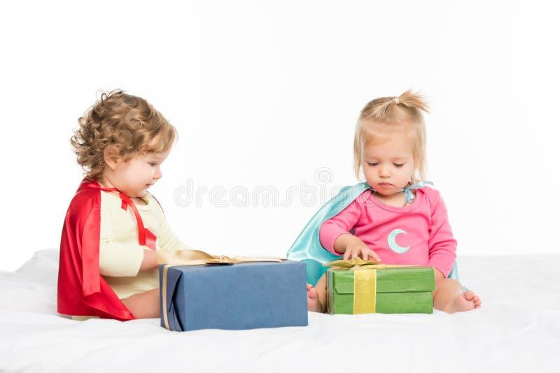 bambini adorabili nei capi del supereroe con i regali avvolti fotografie stock libere da diritti