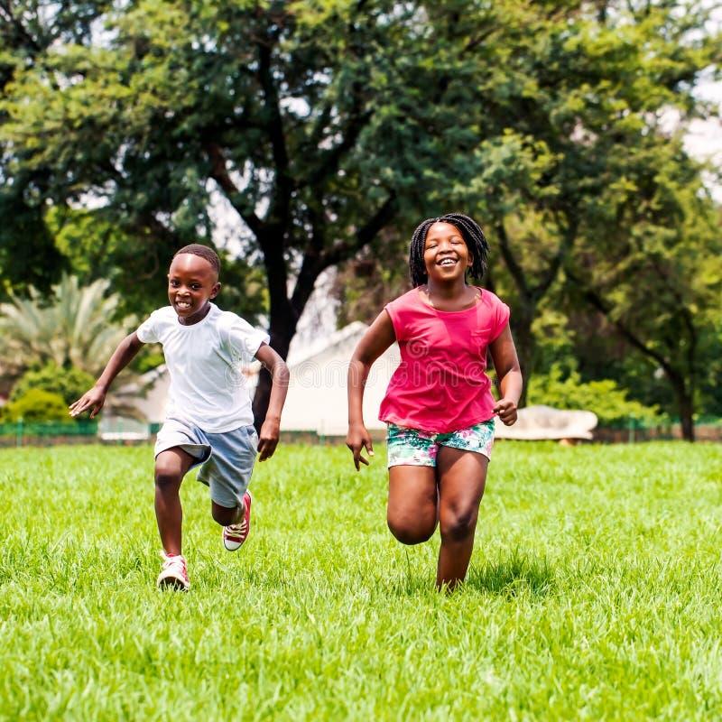 Bambini africani che corrono insieme nel parco fotografia stock