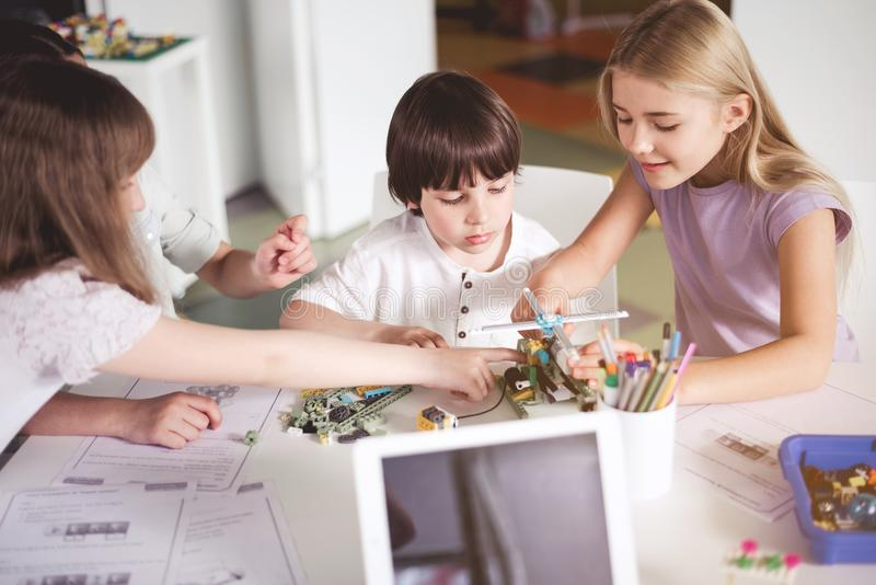 Bambini allegri che creano robot durante la lezione fotografie stock libere da diritti