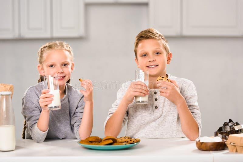 bambini allegri che mangiano i biscotti e latte alimentare alla tavola fotografie stock libere da diritti