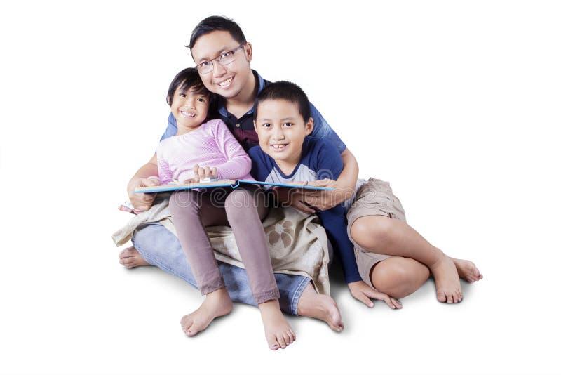 Bambini allegri con il papà che legge un libro immagini stock