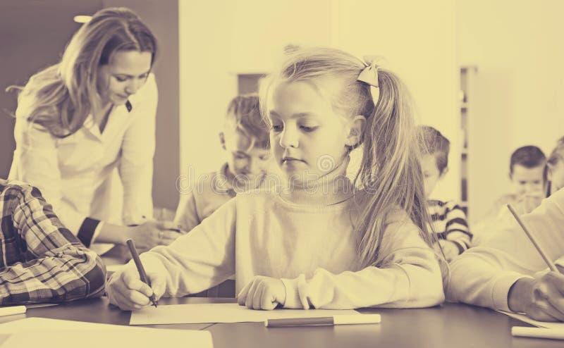 Bambini allegri con l'insegnante che assorbe aula immagini stock libere da diritti