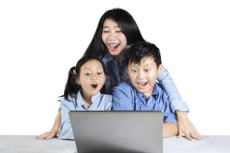 Bambini allegri e sguardo della madre al computer portatile fotografia stock libera da diritti