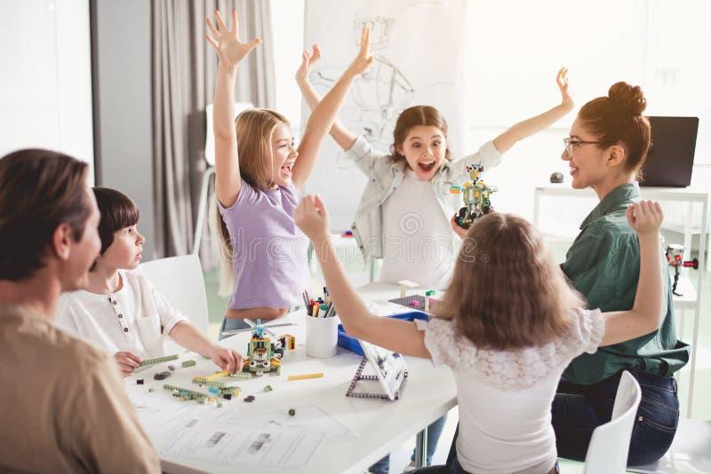 Bambini allegri ed insegnante che fanno giocattolo di plastica fotografia stock libera da diritti