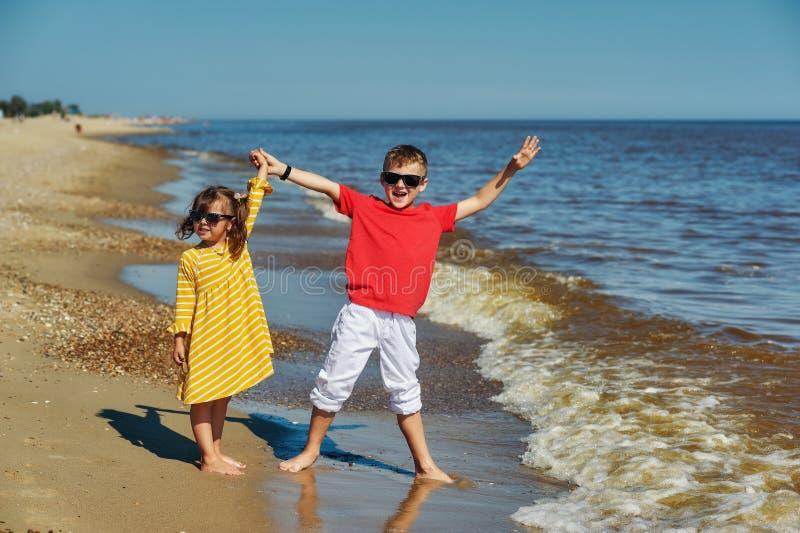 Bambini allegri sulla costa di mare immagini stock