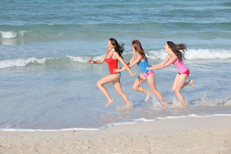 Bambini, anni dell'adolescenza che funzionano sulla vacanza della spiaggia fotografia stock libera da diritti
