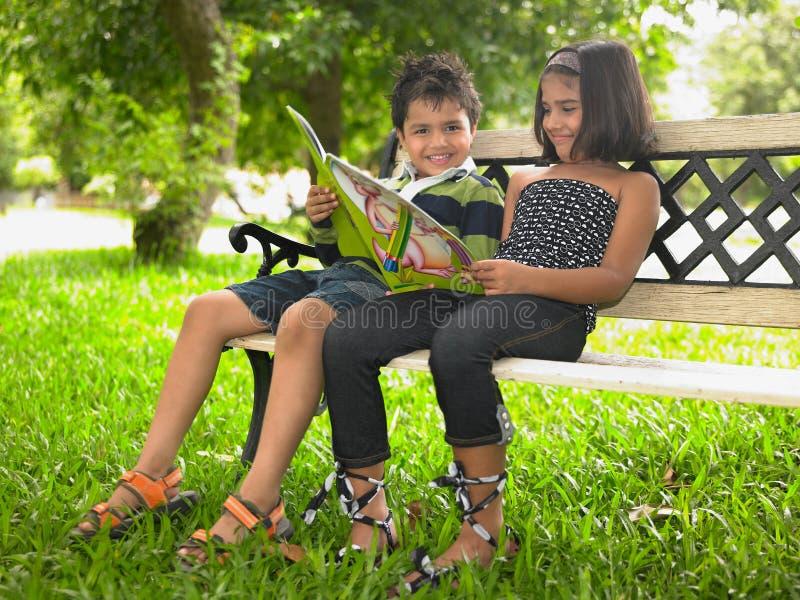 Bambini asiatici che leggono nella sosta fotografia stock libera da diritti