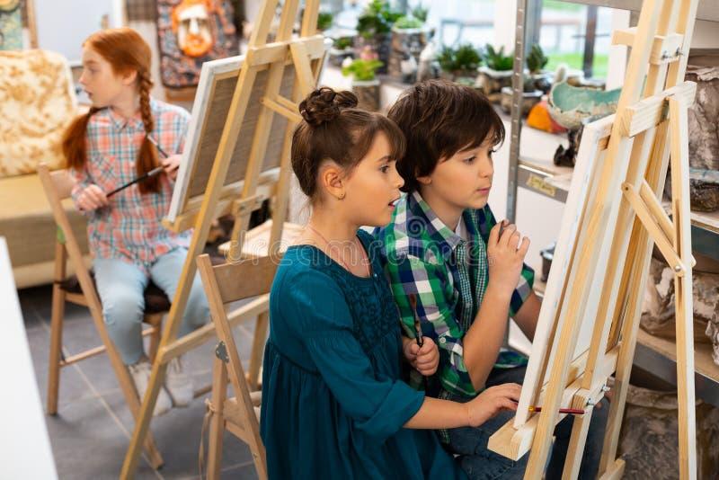 Bambini attivi che ritengono emozionanti mentre assorbendo scuola di arte fotografie stock