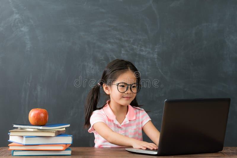 Bambini attraenti della ragazza di bellezza che per mezzo del computer portatile fotografie stock libere da diritti