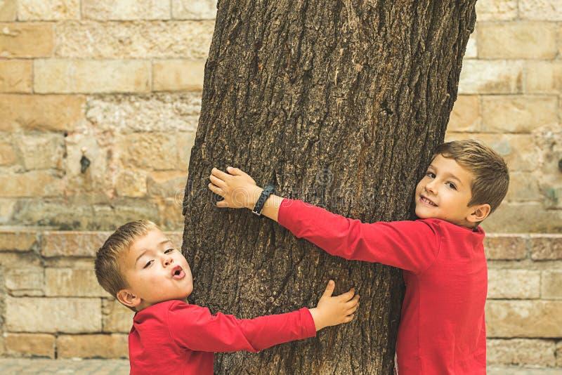 Bambini che abbracciano un albero fotografie stock libere da diritti