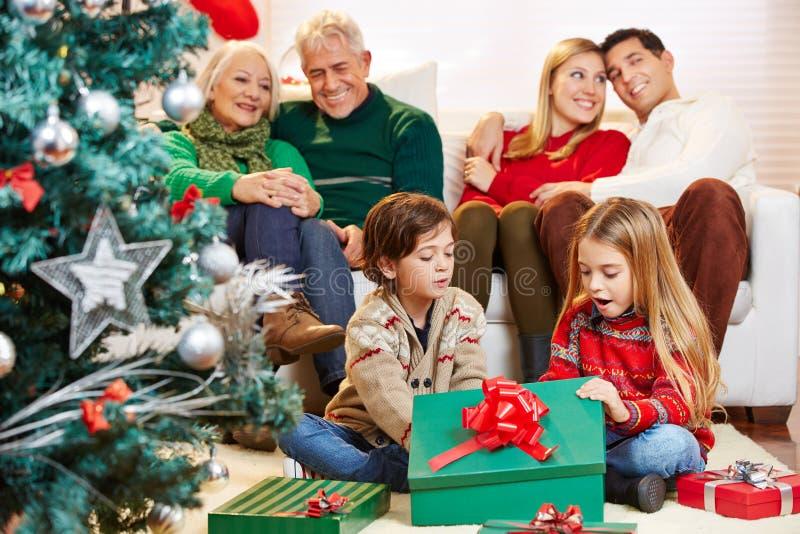 Bambini che aprono i regali al natale immagine stock libera da diritti
