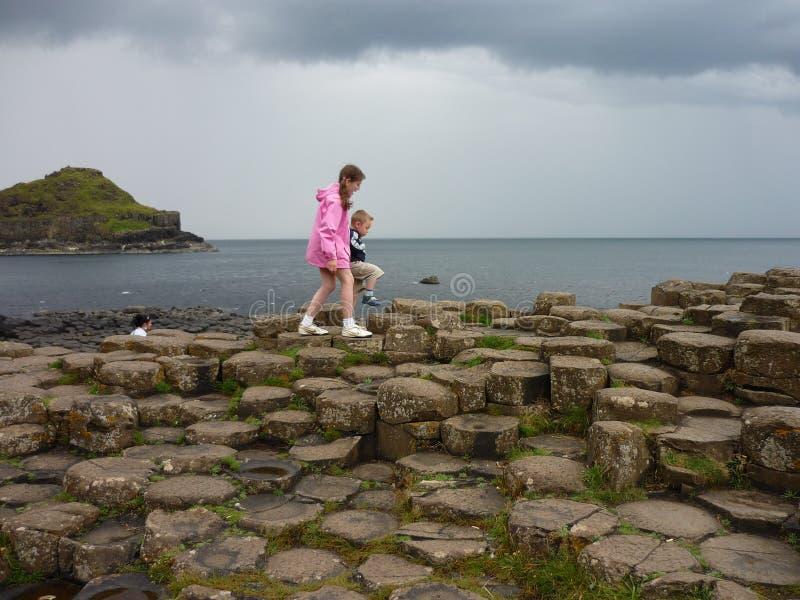 Bambini che camminano sulle colonne del basalto della strada soprelevata del gigante immagine stock