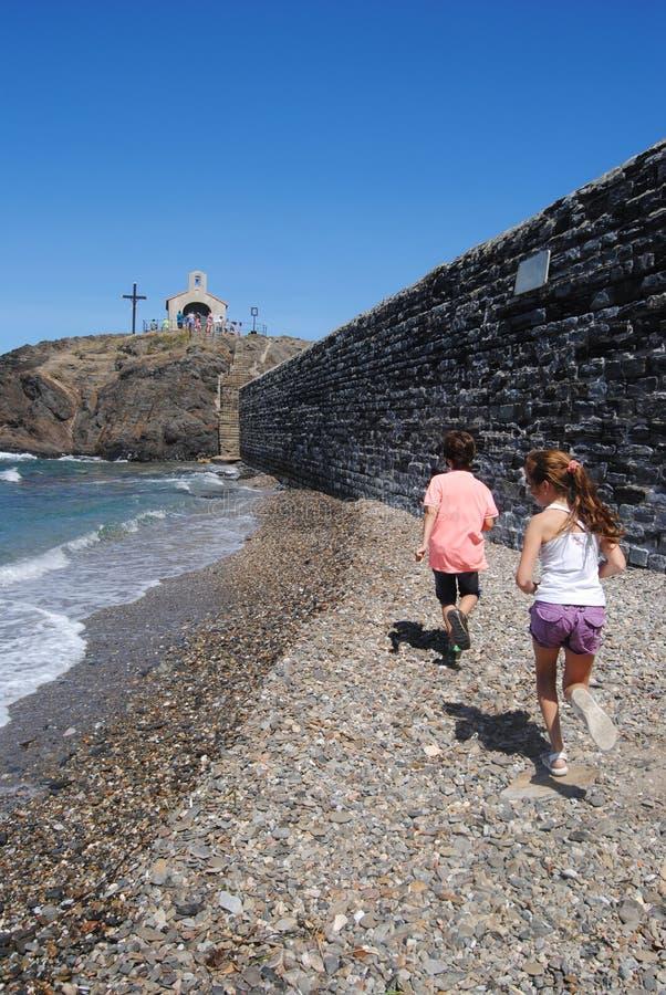 Bambini che cercano le pietre in una spiaggia di Collioure, Colliure, piccolo villaggio francese con una fortezza in un giorno so fotografie stock