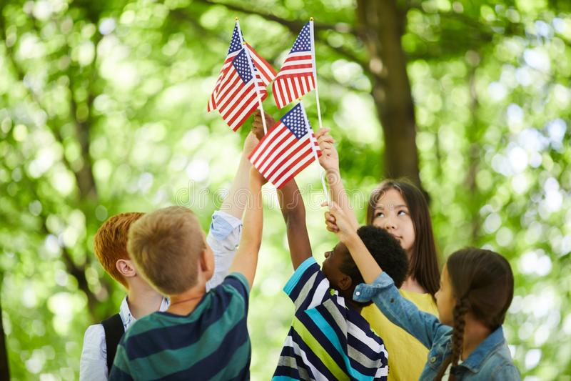 Bambini che ci alzano per attaccare insieme le bandiere immagini stock libere da diritti