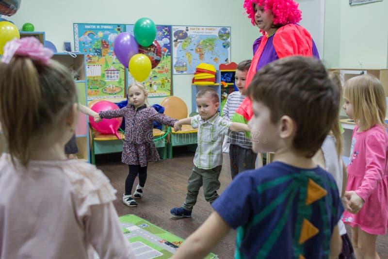 Bambini che conducono ballo rotondo nell'asilo Spettacolo dei bambini russi al partito di buon compleanno fotografia stock