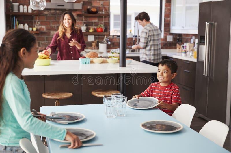 Bambini che contribuiscono a porre da portare in tavola per il pasto della famiglia immagine stock libera da diritti