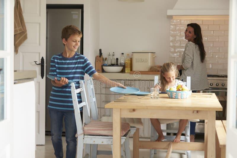 Bambini che contribuiscono a porre Tabella per il pasto della famiglia fotografie stock