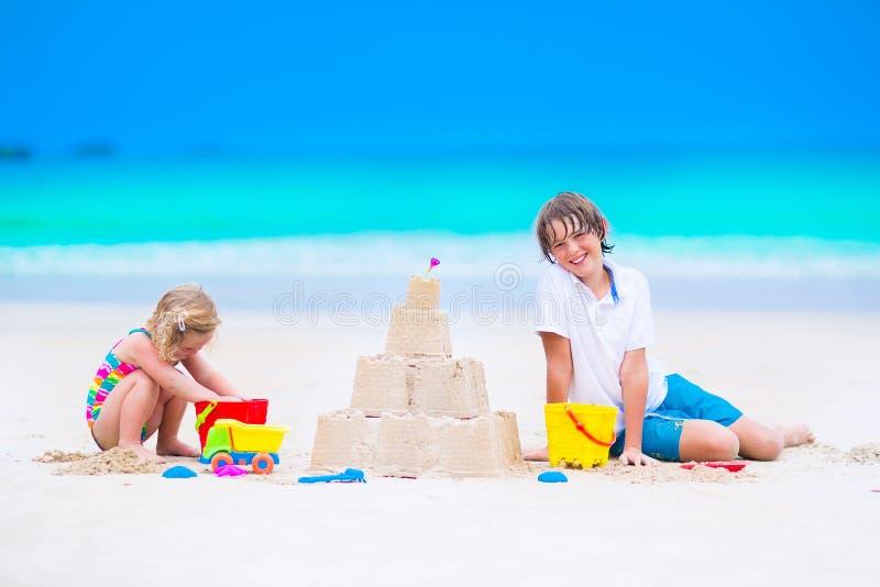 Bambini che costruiscono il castello della sabbia sulla spiaggia fotografia stock