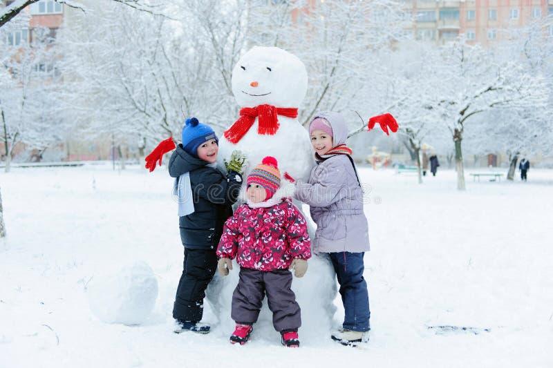 Bambini che costruiscono pupazzo di neve nel giardino immagine stock
