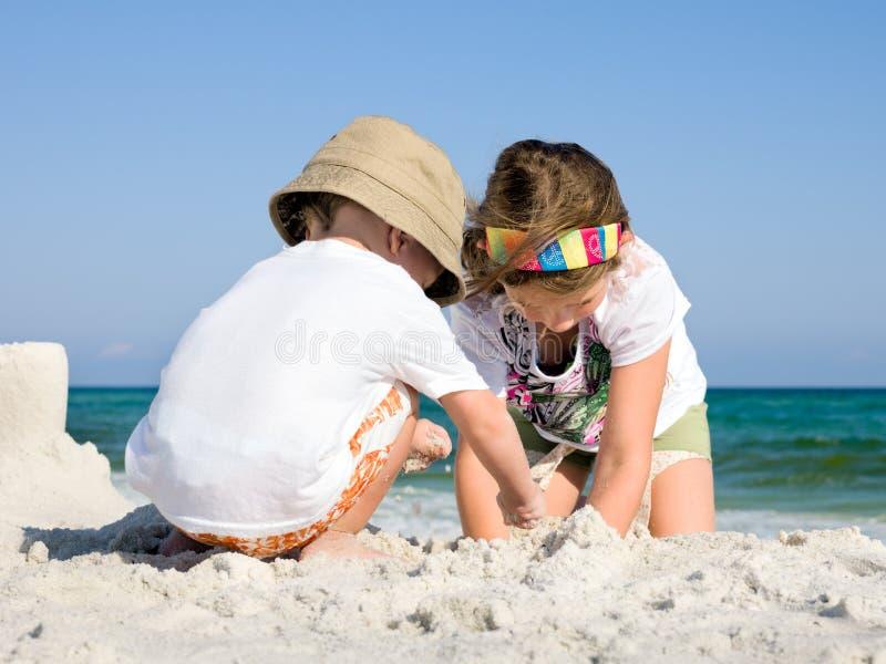 Bambini che costruiscono Sandcastle su una spiaggia immagini stock libere da diritti