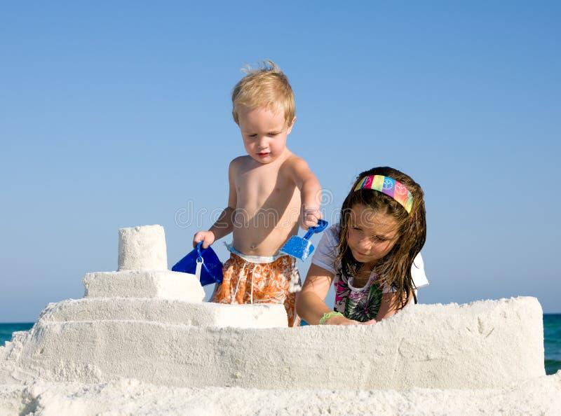 Bambini che costruiscono Sandcastle su una spiaggia immagine stock