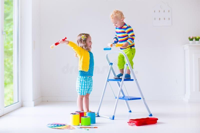Bambini che dipingono le pareti a casa fotografia stock