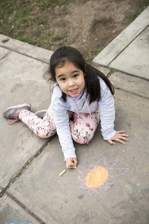 Bambini che disegnano con il gesso sul marciapiede immagini stock libere da diritti