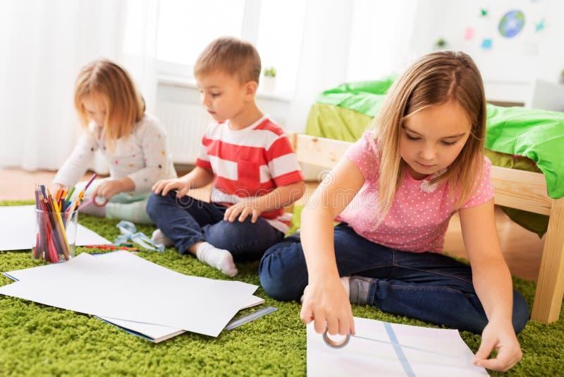 Bambini che disegnano e che fanno i mestieri a casa fotografie stock