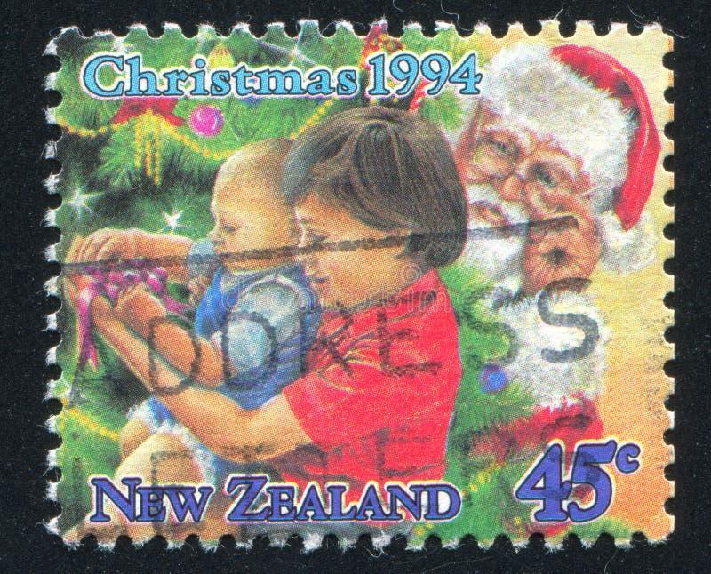 Bambini che disimballano i presente sotto l'albero di Natale fotografia stock