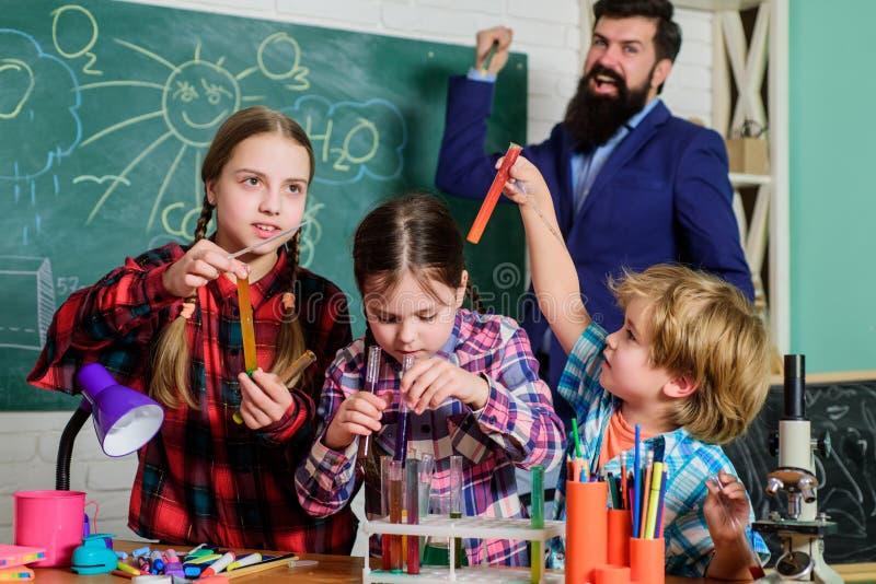 Bambini che fanno gli esperimenti di scienza Istruzione Laboratorio di chimica insegnante felice dei bambini Di nuovo al banco fa immagine stock