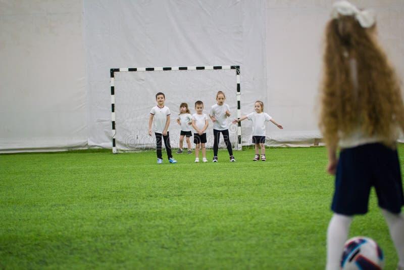 Bambini che giocano a calcio all'interno Il gruppo protegge i portoni da un attacco della bambina fotografia stock