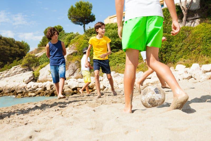 Bambini che giocano a calcio a piedi nudi sulla spiaggia sabbiosa immagini stock libere da diritti