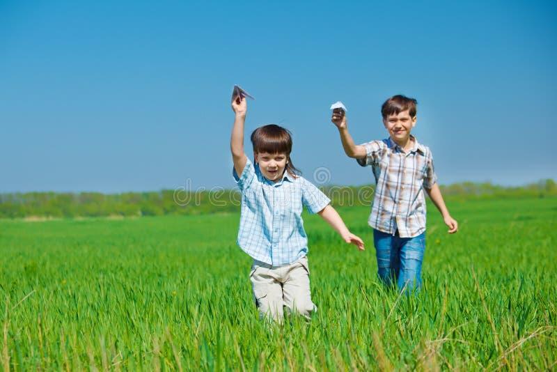 Bambini che giocano con gli aeroplani di carta fotografia stock libera da diritti