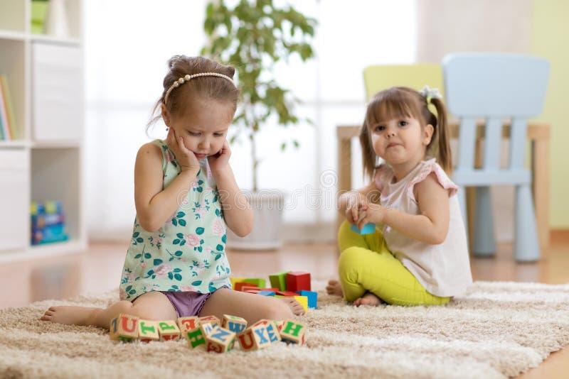 Bambini che giocano con i cubi del giocattolo nella stanza di asilo fotografie stock