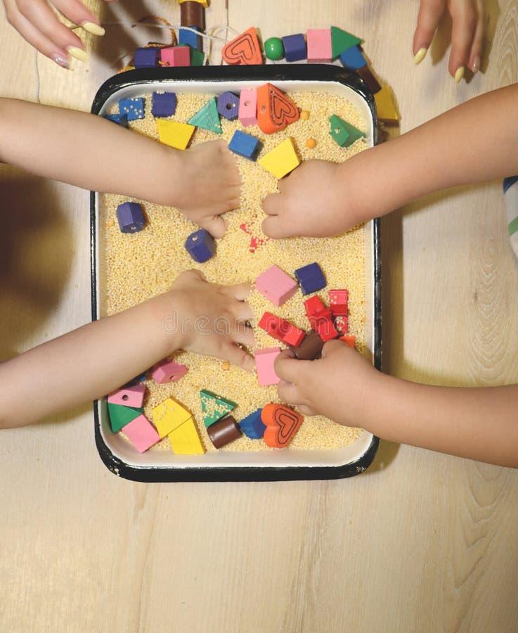 Bambini che giocano con la sabbia, il croup ed il progettista cinetici in scuola materna Lo sviluppo del concetto fine del motore fotografie stock