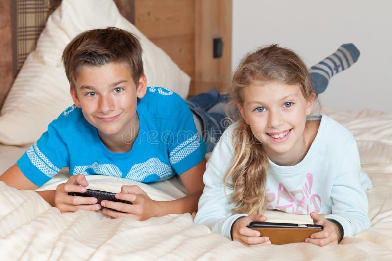 Bambini che giocano con lo smartphone su un letto fotografia stock libera da diritti