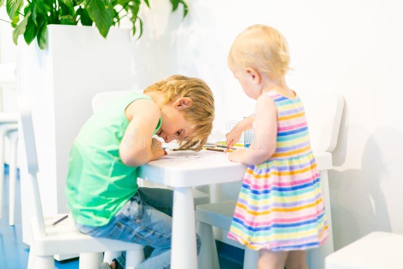 Bambini che giocano e che assorbono i bambini tavola, angolo di attività fotografie stock