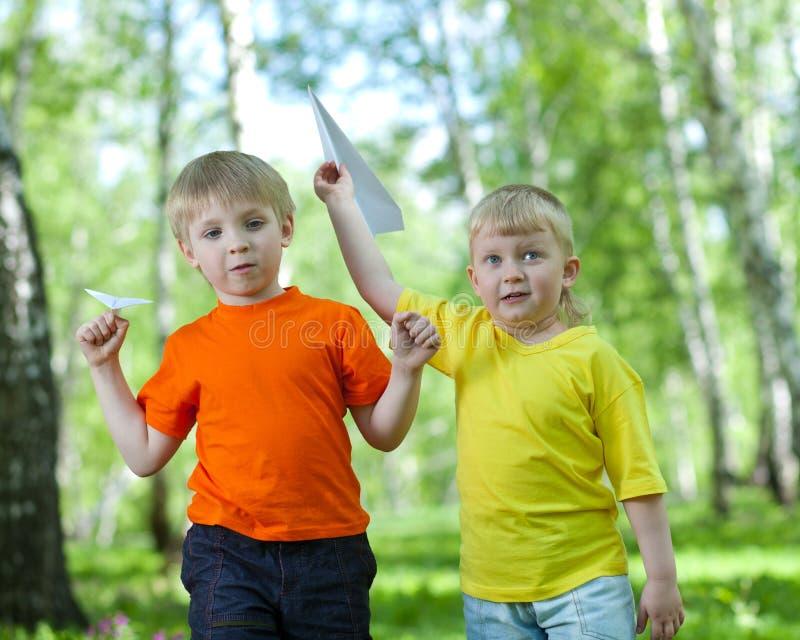 Bambini che giocano e che pilotano un aeroplano di carta fotografie stock libere da diritti