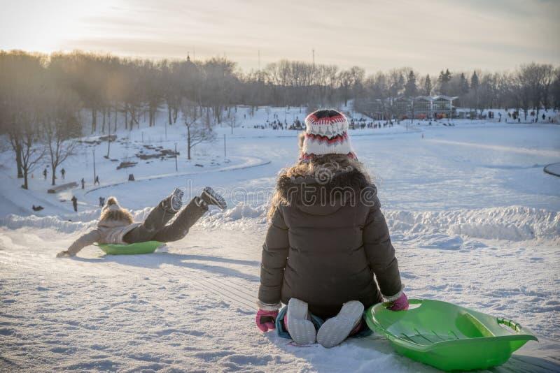 Bambini che giocano fuori con la loro slitta sulla neve fotografia stock
