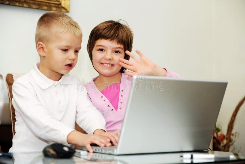 Bambini che giocano i giochi sul computer portatile fotografia stock