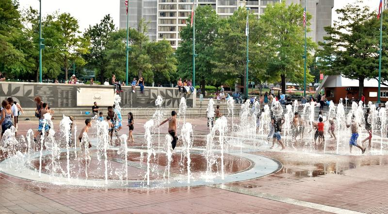 Bambini che giocano il giorno di estate caldo alla fontana degli anelli | Georgia World Congress Center Authority immagini stock