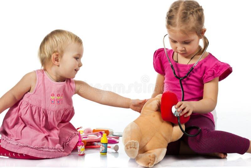 Bambini che giocano medico con una bambola fotografia stock