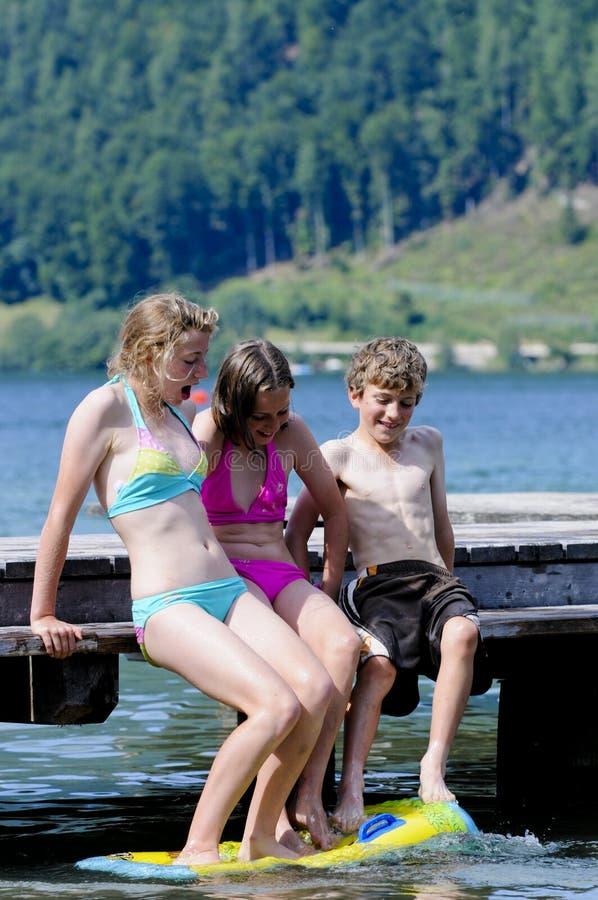Bambini che giocano nel lago immagine stock
