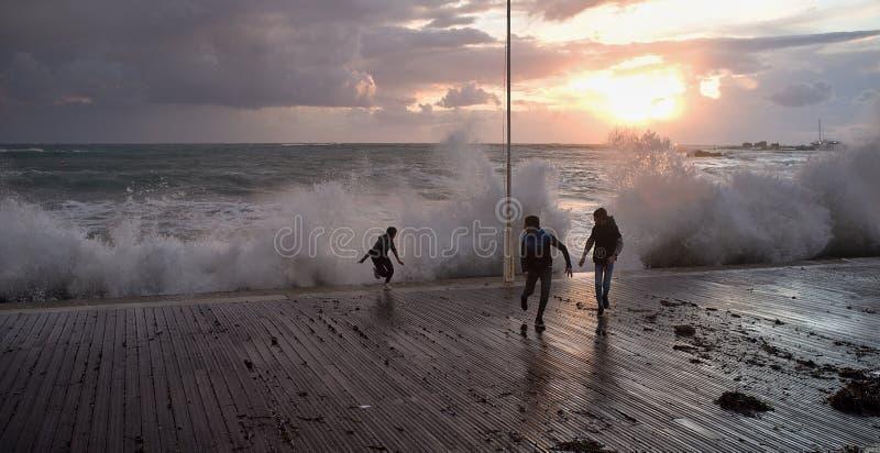 Bambini che giocano nel mare tempestoso fotografia stock libera da diritti
