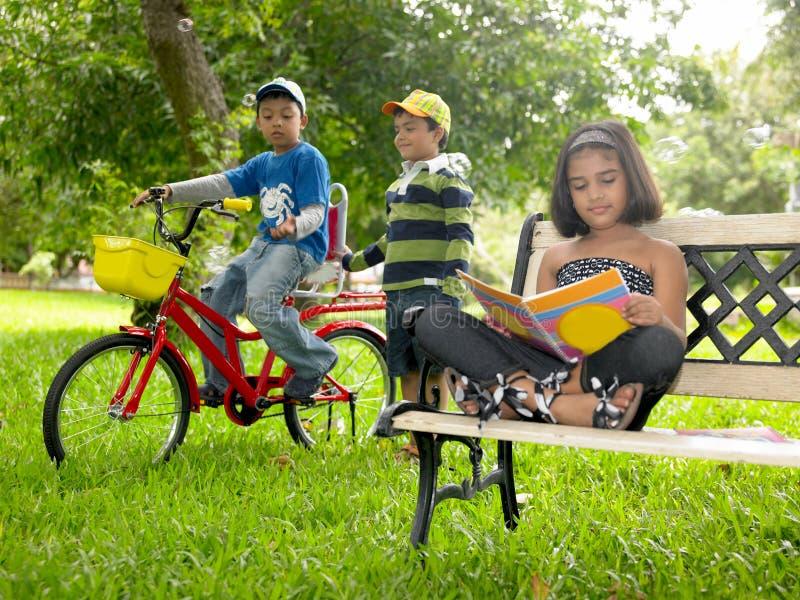 Bambini che giocano nella sosta fotografia stock libera da diritti
