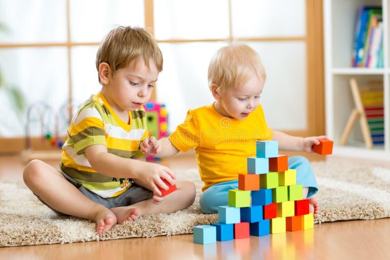 Bambini che giocano nella stanza di bambini immagini stock libere da diritti