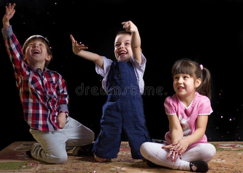 Bambini che giocano su un fondo nero fotografie stock