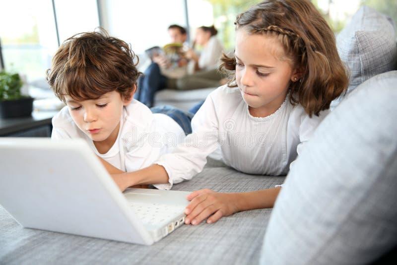 Bambini che giocano sul computer portatile fotografia stock libera da diritti