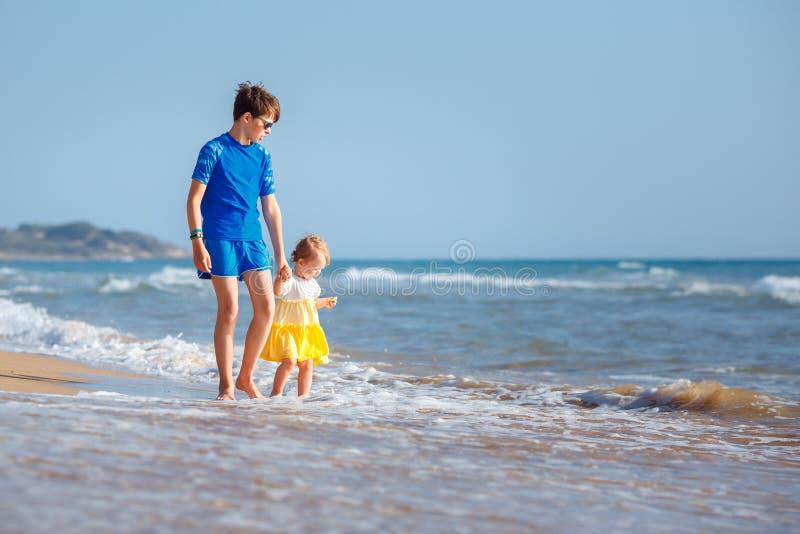 Bambini che giocano sulla spiaggia tropicale Fratello maggiore insieme alla sua sorellina alla riva di mare al tramonto Vacanze e fotografia stock
