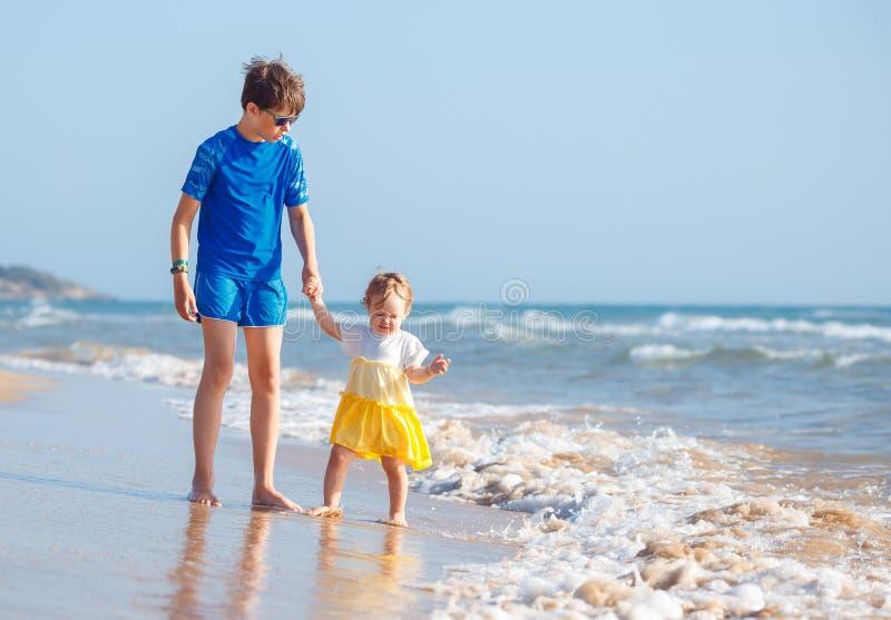 Bambini che giocano sulla spiaggia tropicale Fratello maggiore insieme alla sua sorellina alla riva di mare al tramonto Vacanze e immagini stock